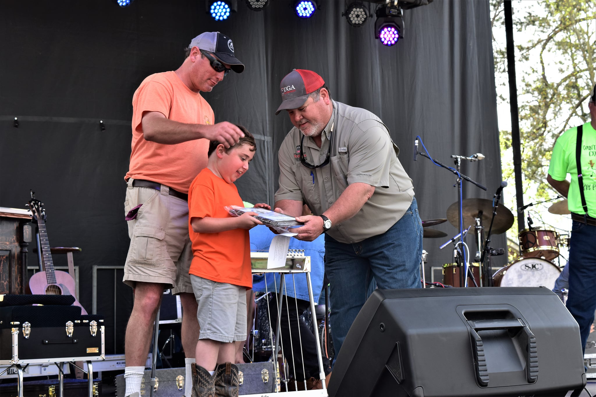 Cleveland (middle) is accompanied by his father (left) and Early County Extension coordinator Brian Cresswell (right) as he is presented with the Farmer of the Year award during the county's annual Peanut Proud parade.